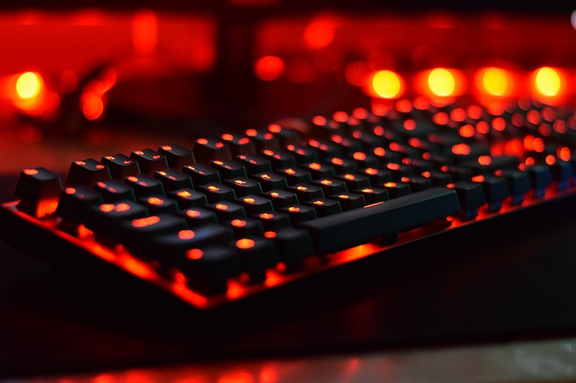 Close up of a mechanical keyboard with the keys lit up with red LEDs