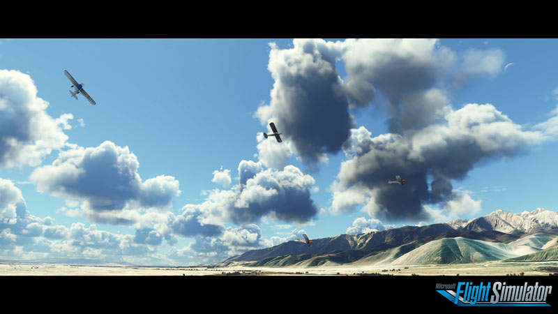 Screen capture from Microsoft Flight Simulator 2020 taken from the ground showing 3 planes in the sky amongst clouds with a mountain range in the background