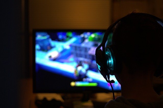 Image taken from behind a gamer wearing a headset as they look forward at their monitor which is blurry in the background