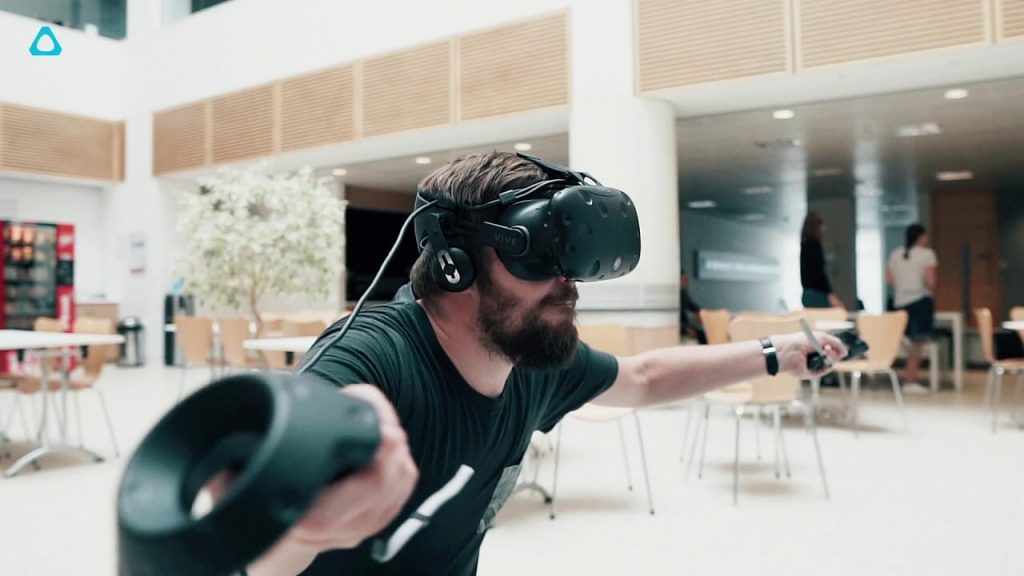 Photo of a man using the HTC Vive headset and controllers