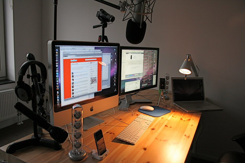 Image of a streaming desk setup including multiple monitors, a microphone and a camera