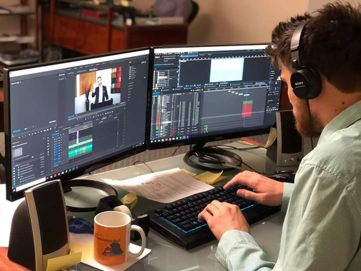 Image of a man editing a video on a PC with two monitors