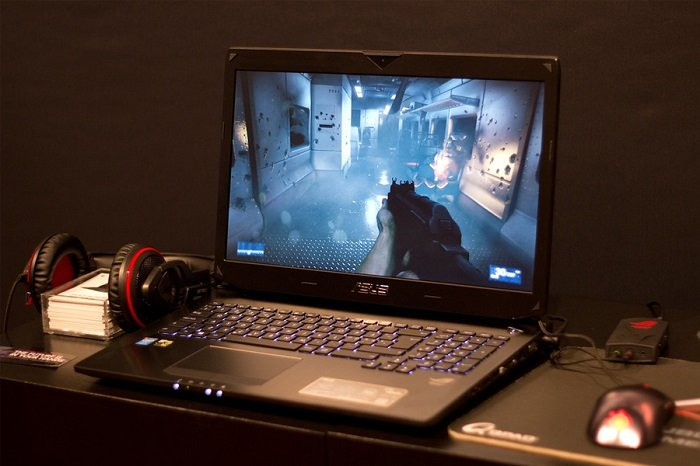 Image of an Asus gaming laptop open on a desk and playing an FPS game