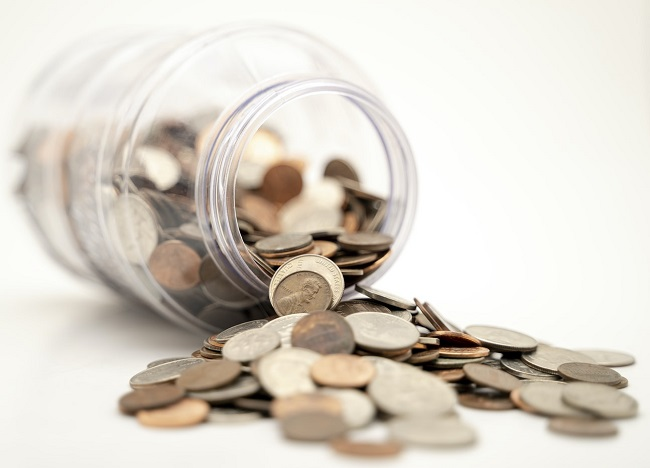 Image of some coins spilling out onto a white table from inside a jar