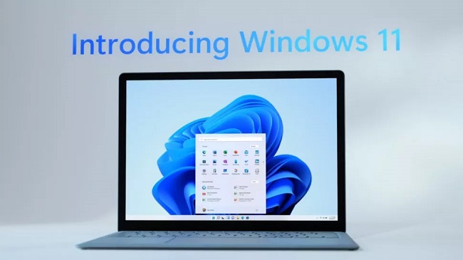 Promotional image for Microsoft Windows 11 showing a laptop open with Windows 11 on screen with the words 'Introducing Windows 11' on the wall behind it